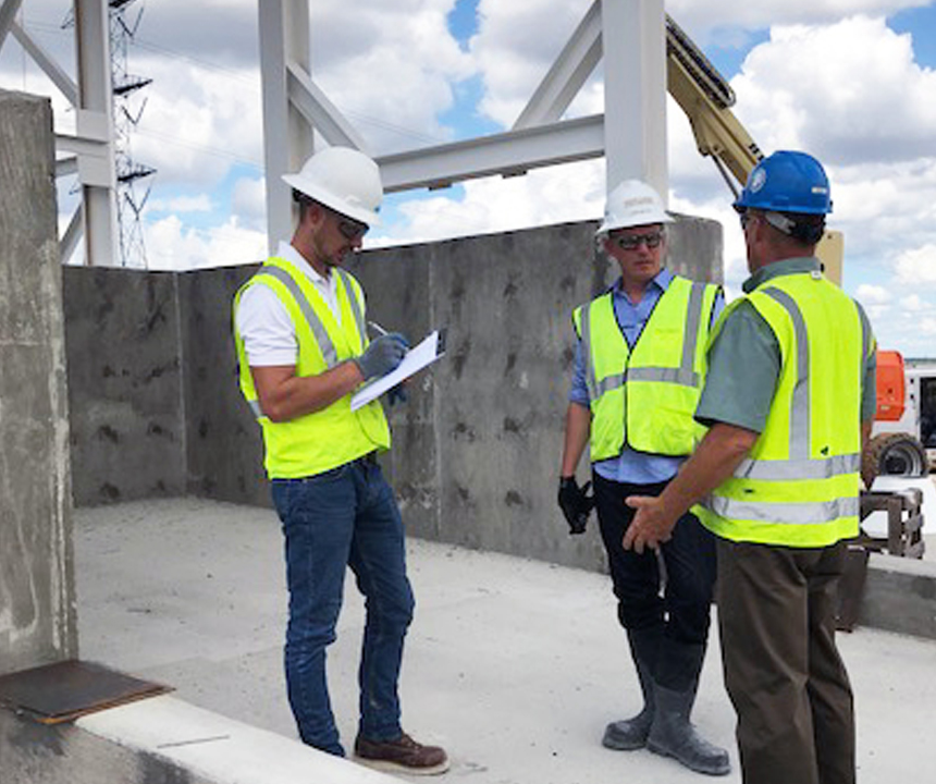 workers onsite reviewing a clipboard checklist